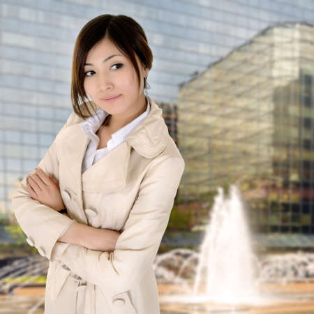 Photo pour Successful young executive woman of Asian standing with modern building exterior. - image libre de droit