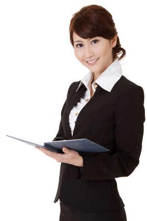 Foto de Asian executive woman smiling and looking at you holding book, half length closeup portrait on white background. - Imagen libre de derechos