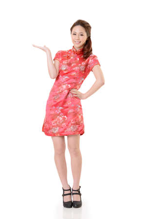 Smiling Chinese woman dress traditional cheongsam and introduce on white background.