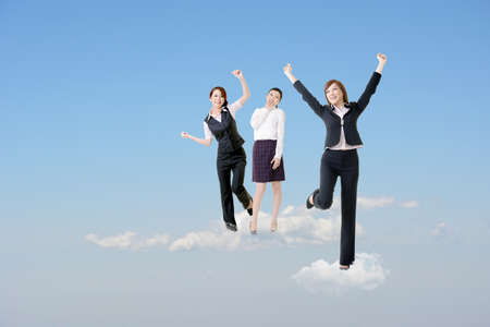 Photo pour Cheerful three Asian business women stand on clouds and raise their arms feel freedom and exciting over blue sky.  - image libre de droit