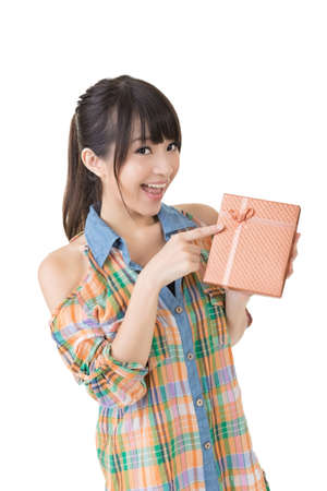 Young smiling asian woman pointing with finger on a gift. Half length potrait. Isolated on the white background.