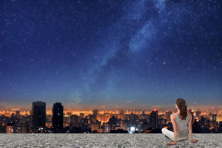 Asian woman sitting on roof, back to camera, and looking on the night city under starry sky.