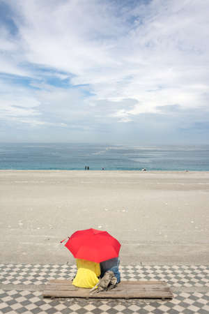 Couple sitting on beach under red umbrella. Shot at famous attraction, Qixingtan Beach in Hualien, Taiwan, Asia.