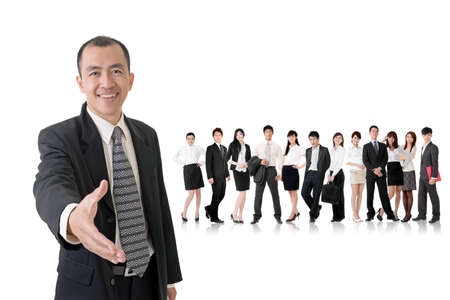 Confident businessman shake hand with you and standing in front of his team on studio white background.の写真素材