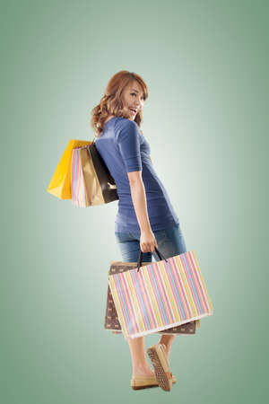 Cheerful shopping woman of Asian holding bags, full length portrait isolated.