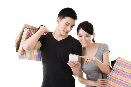 Foto de young Asian couple shopping and looking at cellphone - Imagen libre de derechos