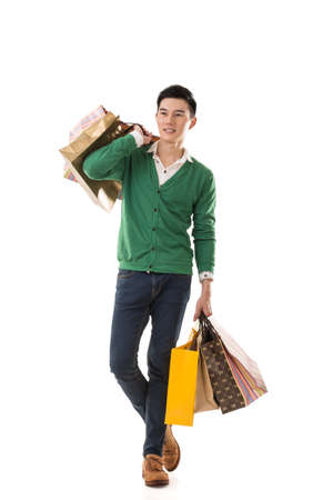 Foto de Asian young man holding shopping bags, full length portrait isolated. - Imagen libre de derechos