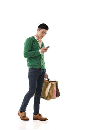 Photo pour Asian young man holding shopping bags and using cellphone, full length portrait isolated. - image libre de droit