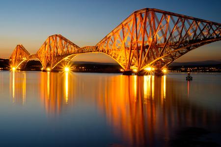The Forth rail bridge illuminated at dawn
