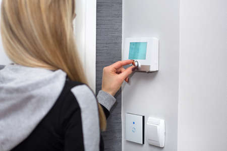 Photo pour Girl adjusts and regulate the room temperature on smart switch on wall. Smart WiFi light switch and temperature regulator. Smart house concept. Close up, selective focus - image libre de droit