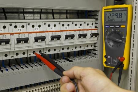 Photo pour Electrical engineer measuring voltage on a miniature circuit breaker. - image libre de droit