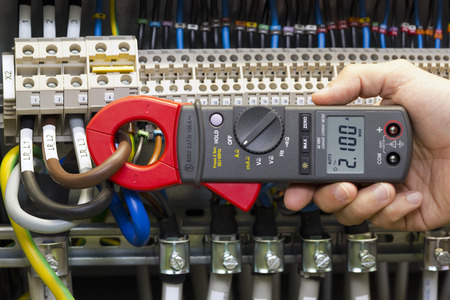 Electrician measuring current with current clamp.