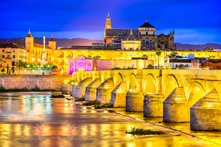 Cordoba, Spain. Roman Bridge on Guadalquivir river and The Great Mosque (Mezquita Cathedral) at twilight in the city of Cordoba, Andalusia.