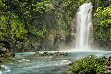 Foto per Beautiful Rio Celeste Falls with swimmer, Tenorio National Park, Costa Rica. - Immagine Royalty Free