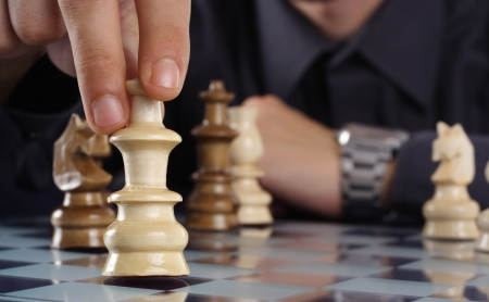 Businessman playing chess game makes his move