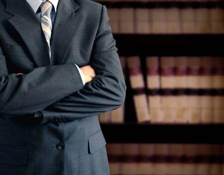 Photo pour Businessman wearing a suit in front of a bookcase  - image libre de droit