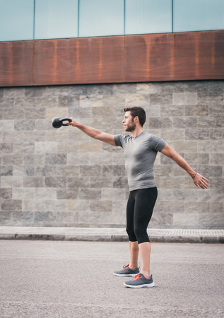 Fitness equipment outside. Sporty man exercising outdoor on the street.