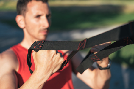 Sporty male training arms and back with trx fitness straps outdside. Workout healthy lifestyle sport concept.