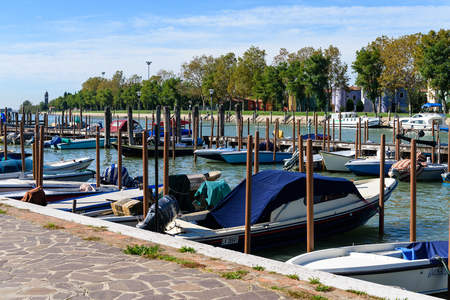 Burano, Italy - October 7, 2017: Moored fishing and transport boats at small harbor on Burano island, Venice lagoon
