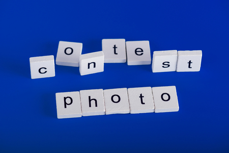 Photo Contest phrase made of white wooden blocks on blue background