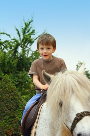 Smiling, young boy ride a pony horse