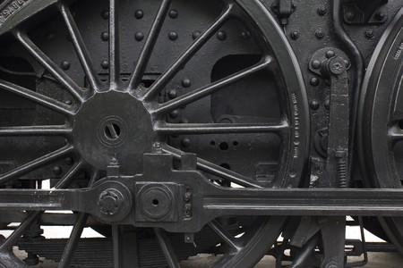 Closeup of vintage steam engine's black, iron wheel