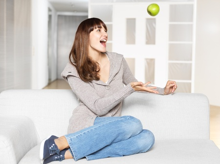 Young woman throwing apple