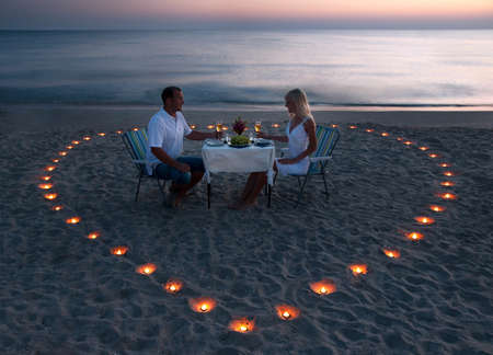 Photo pour A young couple share a romantic dinner with candles heart on the sea sand beach - image libre de droit