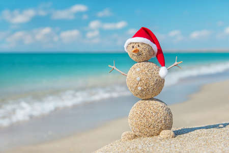 Smiley sandy snowman in santa hat. Holiday concept for New Years and Christmas Cards.
