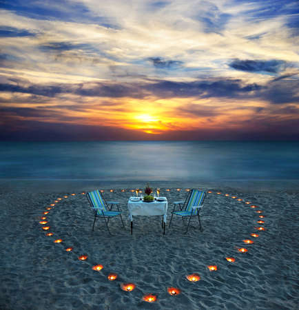 romantic dinner on sea beach with candle heart in Maldives