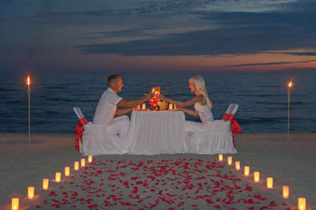 couple share a romantic dinner with candles, torches and way or rose petals at sea sandy beach against sunset