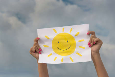 Photo pour human hands with sheet of paper with sun image against overcast sky - positive thinking concept - image libre de droit