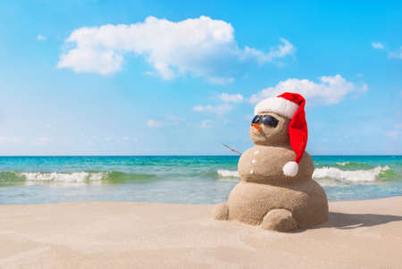 Foto de Sandy christmas snowman in red santa hat and sunglasses at sunny beach. Holiday concept for New Years Cards. - Imagen libre de derechos