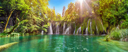 Foto de Amazing waterfall panorama in Plitvice Lakes National Park, Croatia, Europe. Majestic view with turquoise water and sunset sunny beams, travel destinations background - Imagen libre de derechos