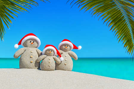 Photo for Positive sandy Snowmen family in red Santa hats at sunny ocean tropical palm beach. Happy New Year and Merry Christmas concept for hot travel destinations natural background. - Royalty Free Image