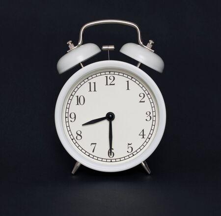 Foto de Old-style alarm clock, black and white, it's half past eight. - Imagen libre de derechos