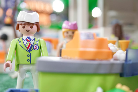 BANGKOK - MAY 6, 2016 : Portrait shot of Playmobil Shop assistant in green uniform standing behind the cashier. Customer service. Playmobil belongs to a toy company, the Brandstatter Group, in Germany