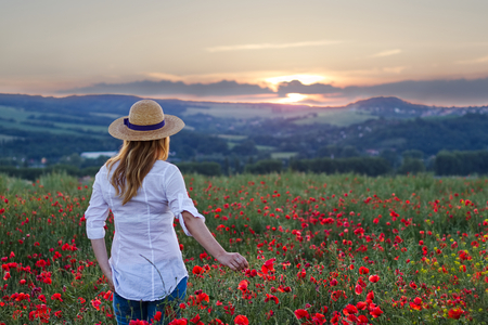 Woman standing in poppy field and enjoying a sunset. Beautiful woman wearing white shirt, jeans and straw hat. Relaxing in nature during sunset. の写真素材