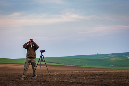 Photo for Wildlife photographer looking for animals by binoculars in nature. Rural scene know as Moravian Tuscany, Czech Republic - Royalty Free Image