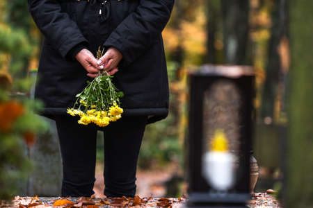 Photo pour Mourning woman holding flowers in hands and standing at grave in cemetery. Sadness during funeral - image libre de droit