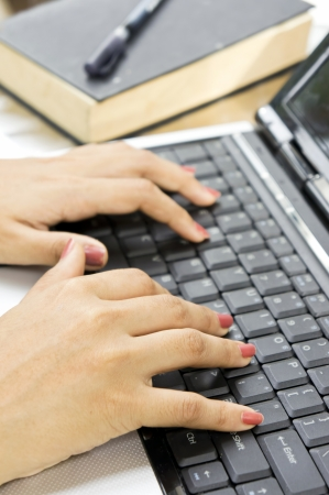 Woman's hands on a notebook keyboard close up - typing
