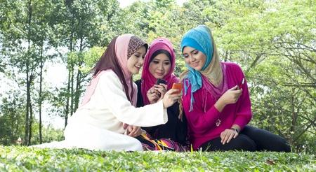 Beautiful young Muslim women having fun with their phone