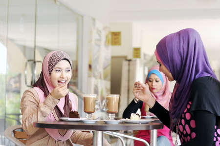 Beautiful Muslim girls chatting at cafe