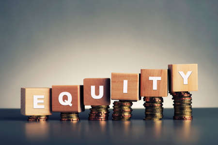 Photo pour equity text written on wooden block with stacked coins on grey background - image libre de droit
