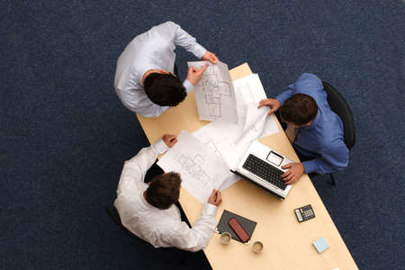 three young executives siting,standing and discussing overblueprints .Aerial shot taken from directly above the table.