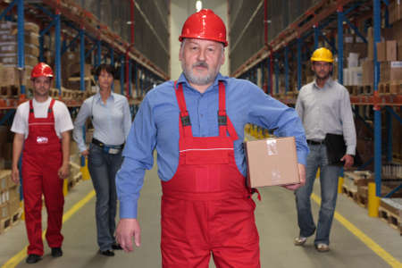mature worker with parcel at the front of team  of workforce  in warehouse