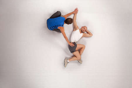 athletic man stretching with personal trainer
