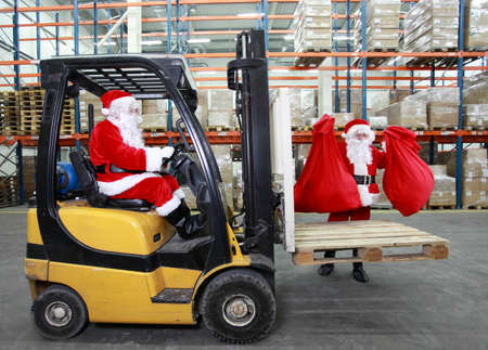 Two Santa clauses working in modern storehouse with gifts