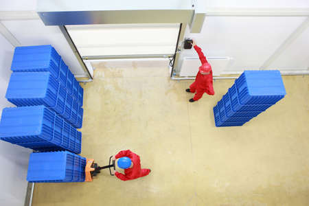 Overhead view of two workers. one is opening a gate another is loading plastic boxes in small warehouse
