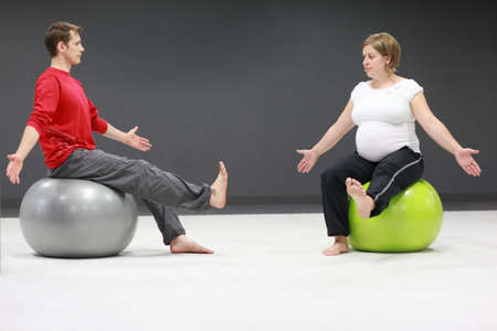 pregnant woman and personal trainer on large stability balls